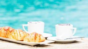 Dos tazas de café con arte y cruasanes del latte Fotos de archivo libres de regalías