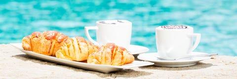 Dos tazas de café con arte y cruasanes del latte Fotos de archivo