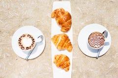 Dos tazas de café con arte y cruasanes del latte Fotografía de archivo