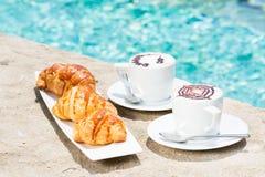 Dos tazas de café con arte y cruasanes del latte Imagenes de archivo