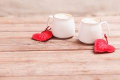 Dos tazas de café con el corazón sentido decorativo en el primer de madera del fondo El concepto del día de tarjeta del día de Sa foto de archivo