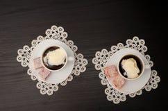 Dos tazas de café con el helado, placer turco en un platillo, en las servilletas blancas del cordón Imagenes de archivo