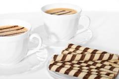 Dos tazas de café con el soplo poner crema de la galleta. Foto de archivo libre de regalías
