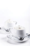 Dos tazas de café con la crema azotada muy blanca Imagen de archivo