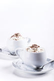 Dos tazas de café con la decoración azotada de la crema y del chocolate Imagen de archivo libre de regalías