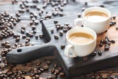 Dos tazas de café con los granos de café Imagenes de archivo