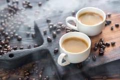 Dos tazas de café con los granos de café Foto de archivo