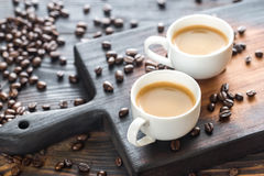 Dos tazas de café con los granos de café Fotos de archivo