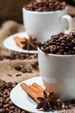 Dos tazas de café con los granos, el anís y el canela de café fotografía de archivo
