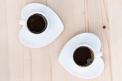 Dos tazas de café con los platillos en forma de corazón Foto de archivo