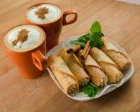 Dos tazas de café con los rollos de canela dulces de la proteína Foto de archivo