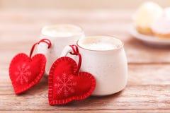 Dos tazas de café con un corazón para el día de tarjeta del día de San Valentín, cumpleaños, la Navidad Fondo de madera Tortas en foto de archivo