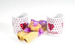 Dos tazas de café con una declaración del amor y de las galletas atados con la cinta en un fondo blanco Fotos de archivo libres de regalías
