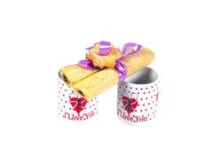Dos tazas de café con una declaración del amor y de las galletas atados con la cinta en un fondo blanco Imagen de archivo libre de regalías