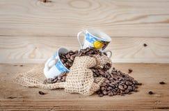 Dos tazas de café decorativas y un bolso del paño con los granos de café Imagenes de archivo