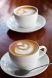 Dos tazas de café del latte en la tabla de madera Imagen de archivo libre de regalías
