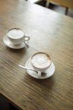 Dos tazas de café en el vector de madera Imagen de archivo libre de regalías
