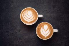 Dos tazas de café en fondo rústico negro Imagenes de archivo