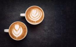 Dos tazas de café en fondo rústico negro Foto de archivo libre de regalías