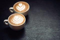 Dos tazas de café en fondo rústico negro Imagen de archivo libre de regalías