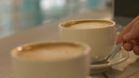 Dos tazas de café en la tabla en cierre de la cafetería para arriba Tazas con café del capuchino almacen de video
