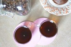 Dos tazas de café en la tabla Una tabla con la placa del desayuno con el mollete, un tarro de granos de café Fotografía de archivo libre de regalías