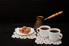 Dos tazas de café en las servilletas del cordón, los potes y el postre turco del chocolate en un fondo negro Imagen de archivo