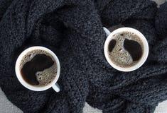 Dos tazas de café envueltas en bufanda de lana negra Imágenes de archivo libres de regalías