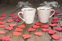 Dos tazas de café, figuras de corazones, en una tabla de madera Fotografía de archivo libre de regalías