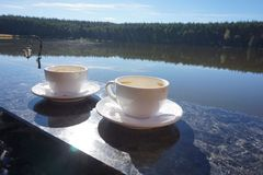Dos tazas de café de la mañana, colocándose en el lado del balcón, con una vista mágica del lago fotografía de archivo libre de regalías
