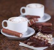 Dos tazas de café o de cacao caliente con los chocolates y las galletas encendido Fotos de archivo