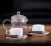 Dos tazas de café o de cacao caliente con los chocolates y las galletas encendido Imagenes de archivo