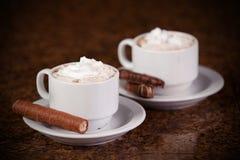 Dos tazas de café o de cacao caliente con los chocolates y las galletas encendido Fotografía de archivo libre de regalías