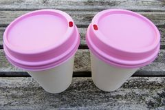 Dos tazas de café de papel con las tapas rosadas en la tabla de madera Imagen de archivo libre de regalías