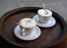 Dos tazas de café que se colocan en las placas con las cucharas del metal Foto de archivo libre de regalías