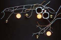 Dos tazas de café, de ramas, de velas y de juguetes de la Navidad en un fondo oscuro fotografía de archivo