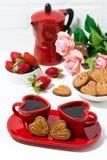 dos tazas de café rojas y galletas en forma de corazón en el fondo blanco Fotografía de archivo libre de regalías