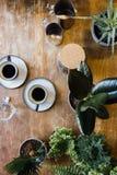 Dos tazas de café sólo en la tabla con las plantas Imágenes de archivo libres de regalías