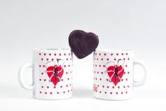 Dos tazas de café y de caramelo bajo la forma de corazón en un fondo blanco - desayune para los amantes Imagen de archivo