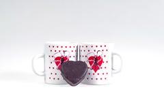 Dos tazas de café y de caramelo bajo la forma de corazón en un fondo blanco - desayune para los amantes Foto de archivo libre de regalías