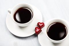 Dos tazas de café y de dulces en forma de corazón Fotos de archivo libres de regalías