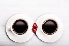 Dos tazas de café y de dulces en forma de corazón Imagen de archivo libre de regalías