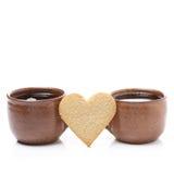 Dos tazas de café y de galletas en la forma del corazón Imagen de archivo libre de regalías
