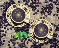 Dos tazas de café y de granos Imágenes de archivo libres de regalías