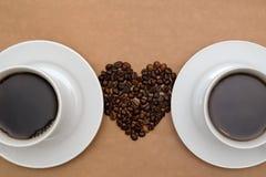 Dos tazas de café y de granos de café en la forma del corazón Imágenes de archivo libres de regalías