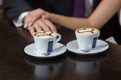 Dos tazas de café y de manos Imágenes de archivo libres de regalías