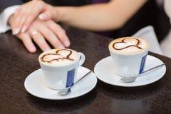 Dos tazas de café y de manos Foto de archivo libre de regalías