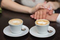 Dos tazas de café y de manos Imagenes de archivo