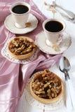 Dos tazas de café y de un postre francés, tarta del caramelo de la nuez Imagen de archivo libre de regalías