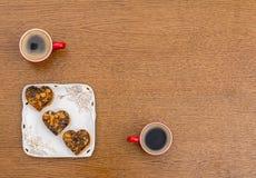 Dos tazas de café y de una placa cuadrada con las tortas Imagen de archivo
